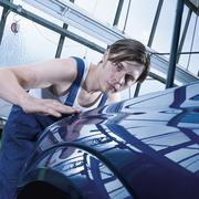 Germany, Augsburg, Worker looking at shiny car after waxing - stock photo