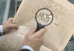 Man holding a magnifying glass over a newspaper - stock photo