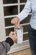 Stock Photo of Teenage boy donating money at door
