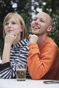 Stock Photo of Germany, Berlin, Young man and woman looking away, smiling
