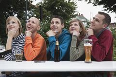 Germany, Berlin, Man and woman looking away and smiling, with hand on chin Stock Photos