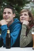 Germany, Berlin, Young man and woman looking away with hand on chin Stock Photos
