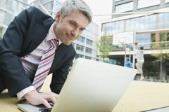 Germany, Hamburg, Business man sitting on floor and using laptop Stock Photos