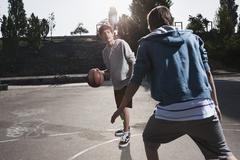 Germany, Berlin, Teenage boys playing basketball in playground - stock photo