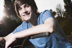 Germany, Berlin, Teenage boy on bike, smiling - stock photo