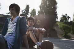 Germany, Berlin, Teenage boys sitting in playground - stock photo