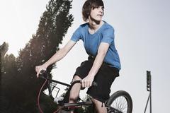 Germany, Berlin, Teenage boy doing stunt on bike - stock photo