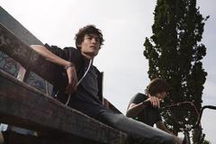 Germany, Berlin, Teenage boy looking away, boy with bike in background Stock Photos