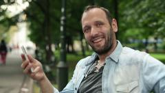 Happy man with smartphone sitting in the park HD Stock Footage