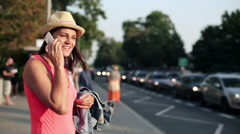 Young woman talking on cellphone by the street HD Stock Footage