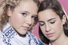 Stock Photo of Two girls against pink background