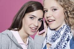 Girls with cell phone, smiling, portrait - stock photo