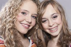 Teenage girl and girl smiling, portrait - stock photo