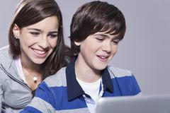 Stock Photo of Girl and boy using laptop, smiling