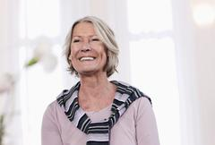 Germany, Wakendorf, Senior woman looking away and smiling Stock Photos