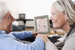 Grandparents holding granddaughter photograph Stock Photos