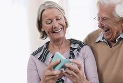 Senior man surprising woman with gift, smiling - stock photo