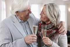 Stock Photo of Senior couple with sparkling wine, smiling