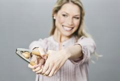 Mid adult woman cracking walnut with nut cracker Stock Photos