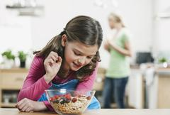 Girl looking at muesli in bowl, mother in background Stock Photos