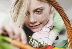 Stock Photo of Girl looking at vegetable, close up