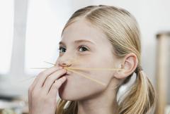 Girl making spaghetti moustache Stock Photos