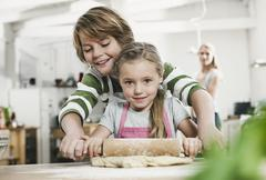 Stock Photo of Germany, Cologne, Boy and girl rolling dough, mother in background