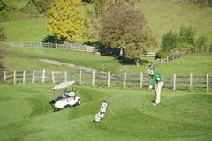 Stock Photo of Italy, Kastelruth, Mature man playing golf on golf course