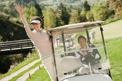 Golfers in golf cart on golf course, smiling Stock Photos