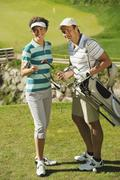 Stock Photo of Golfers on golf course, smiling, portrait