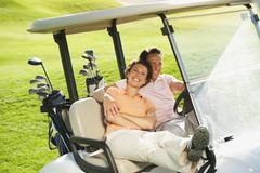 Stock Photo of Golfers sitting in golf cart on golf course, smiling, portrait