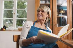 Senior woman with cook book, smiling - stock photo