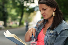 Woman reading book in the park and drink water NTSC Stock Footage