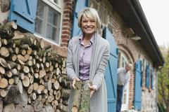 Senior woman with firewood, senior man in background Stock Photos