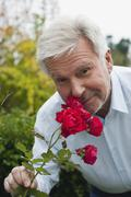 Stock Photo of Germany, Kratzeburg, Senior man smelling roses