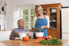 Stock Photo of Germany, Kratzeburg, Senior man with newspaper, senior woman preparing food
