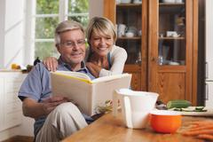 Germany, Kratzeburg, Senior couple reading cook book - stock photo