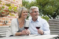 Germany, Kratzeburg, Senior couple with wine glass sitting near country house - stock photo