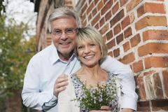 Germany, Kratzeburg, Senior couple with flower bouquet at country house, - stock photo