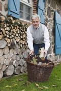 Germany, Kratzeburg, Senior man with basket of fire woods Stock Photos