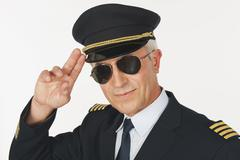Close up of senior flight captain saluting against white background, smiling - stock photo