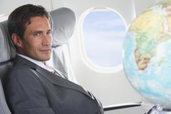 Stock Photo of Germany, Bavaria, Munich, Mid adult businessman looking at globe in business