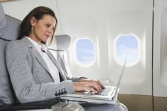 Germany, Bavaria, Munich, Mid adult businesswoman using laptop in business class - stock photo