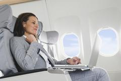 Germany, Bavaria, Munich, Mid adult businesswoman using laptop in business class Stock Photos