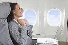 Germany, Bavaria, Munich, Mid adult businesswoman with laptop in business class - stock photo