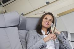Stock Photo of Germany, Bavaria, Munich, Mid adult businesswoman drinking champagne in business