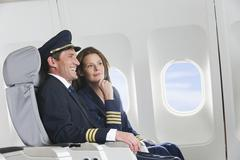 Germany, Bavaria, Munich, Mid adult flight personnels in business class airplane - stock photo