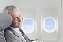 Germany, Bavaria, Munich, Senior businessman sleeping in business class airplane - stock photo