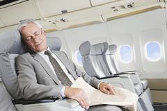 Germany, Bavaria, Munich, Senior businessman sleeping in business class airplane Stock Photos