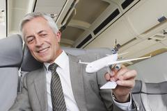 Germany, Bavaria, Munich, Close up of senior businessman with model aeroplane in Stock Photos